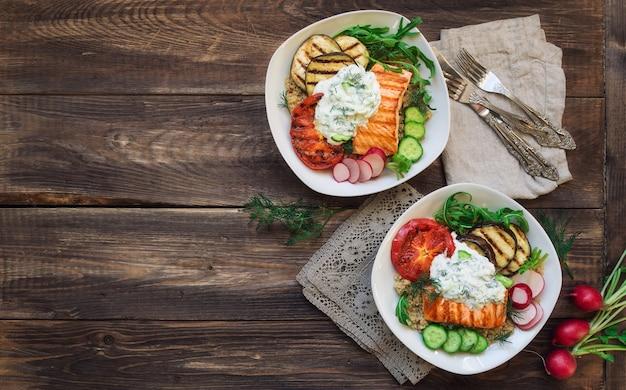 Grillowane bakłażany z łososiem i pomidorami z komosą ryżową i sosem tzatziki na rustykalnym drewnianym tle