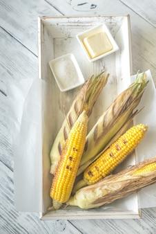 Grillowane corncorbs na drewnianej tacy