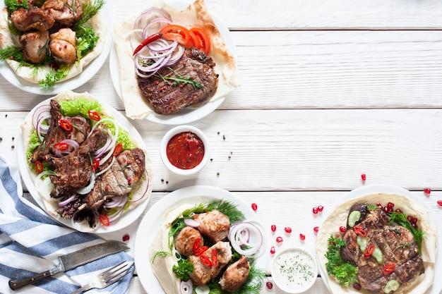 Grillowane dania mięsne na stole. widok z góry na asortyment smacznych przekąsek z grilla, dalej wolne miejsce