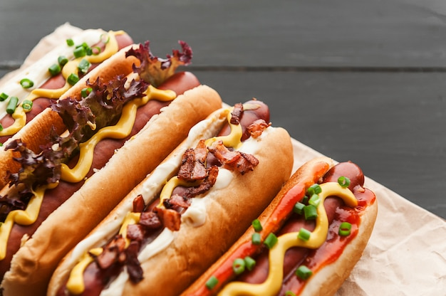 Grillowane hot dogi z żółtą amerykańską musztardą, na ciemnym tle drewniane