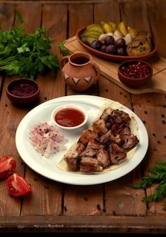 Grillowane kawałki mięsa z boczną cebulą i keczupem