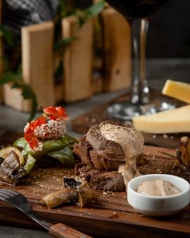 Grillowane kawałki steku z grillowanymi warzywami i sosem, w stylu rustykalnym