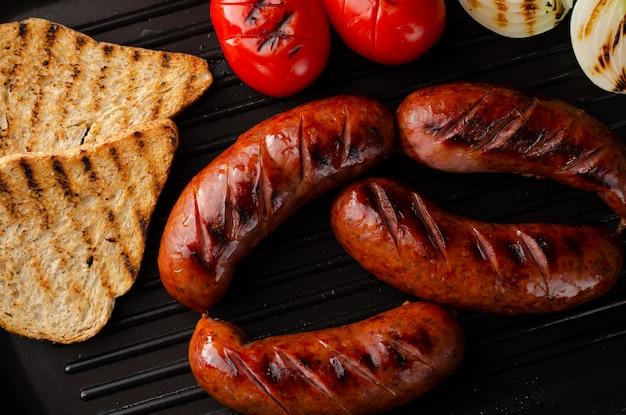 Grillowane kiełbaski grillowane z pomidorami, cebulą i grzankami na patelni grillowej. strzał z góry.