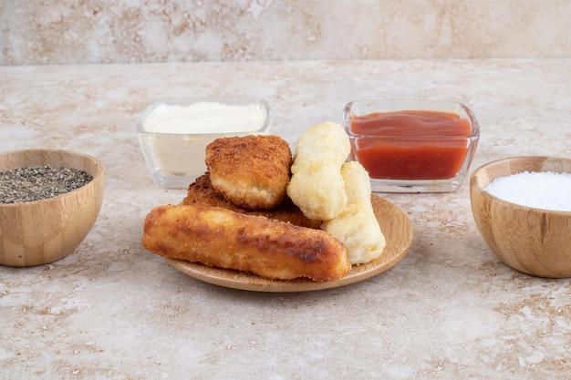 Grillowane kiełbaski i paluszki serowe podawane z sosami.