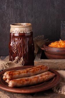 Grillowane kiełbaski, kapusta kiszona, kubek z piwem na drewnianym tle oktoberfest concept