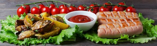 Grillowane kiełbaski na zielonych liściach sałaty, sos pomidorowy, czerwone pomidory czereśniowe na gałęzi. drewniane ciemne