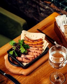 Grillowane kiełbaski podawane z flatbread i zielonymi ziołami