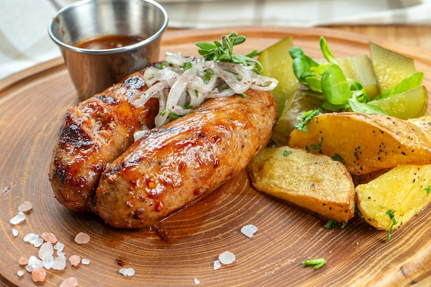 Grillowane kiełbaski w sosie miodowo-piwnym podawane na drewnianej desce z ziołami, smażonymi ziemniakami, kiszonymi ogórkami i kapustą. niemiecka, bawarska kuchnia domowa. selektywne ustawianie ostrości