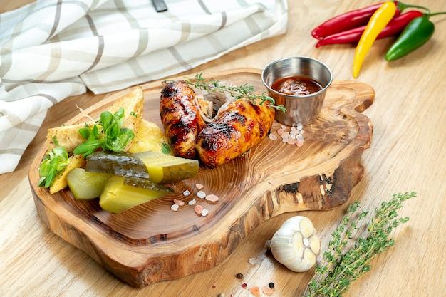 Grillowane kiełbaski w sosie miodowo-piwnym podawane na drewnianej desce z ziołami, smażonymi ziemniakami, kiszonymi ogórkami i kapustą.