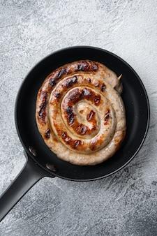 Grillowane kiełbaski z mięsa wieprzowego ustawione na żeliwnej patelni, na szarym tle, widok z góry na płasko