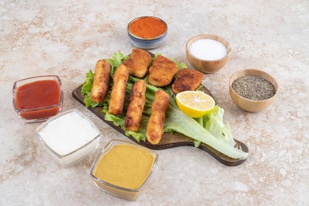 Grillowane kiełbaski z nuggetsami z kurczaka na kawałku sałaty na drewnianej desce z sosami na bok.