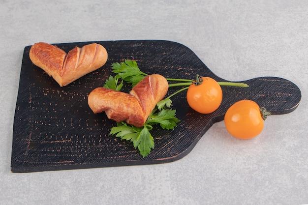 Grillowane kiełbaski z pomidorami na desce.