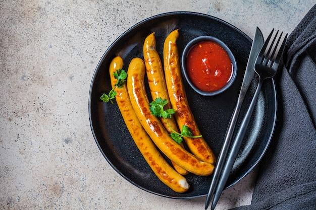 Grillowane kiełbaski z sosem pomidorowym i ziołami na czarnym talerzu.