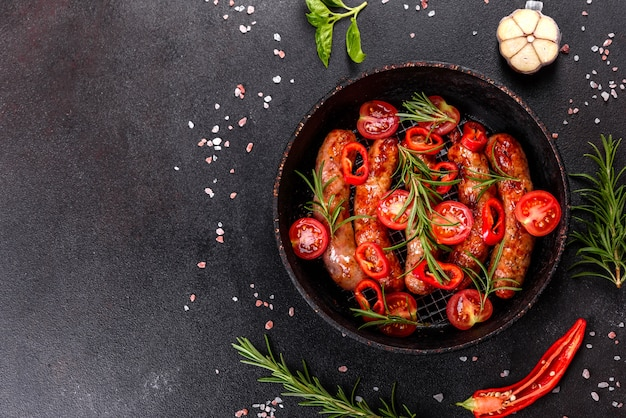 Grillowane kiełbaski z warzywami i przyprawami na czarnym tle