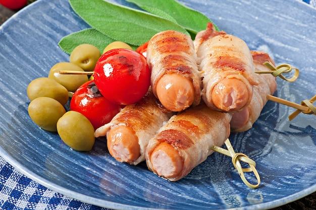 Grillowane kiełbaski zawinięte w paski boczku z pomidorami i liśćmi szałwii