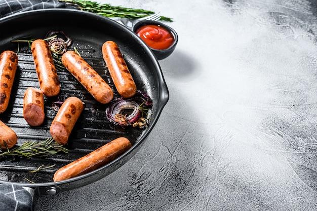 Grillowane klasyczne kiełbaski wieprzowe z cebulą, czosnkiem i rozmarynem na patelni. czarna powierzchnia. widok z góry. skopiuj miejsce