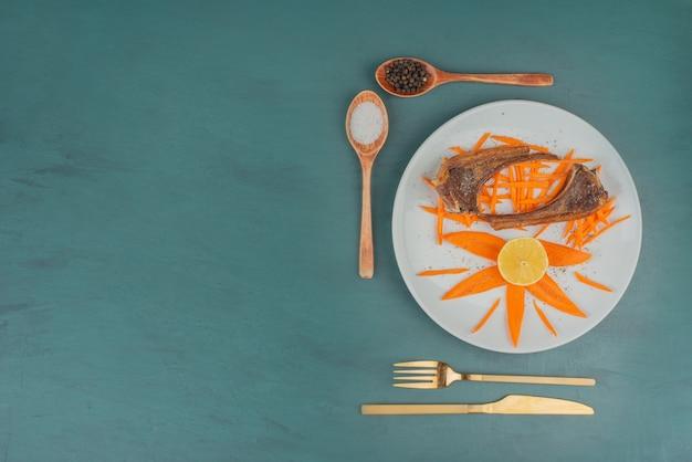 Grillowane kotlety jagnięce na białym talerzu z plastrami marchwi i sztućcami.