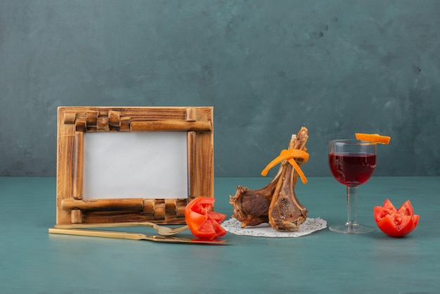 Grillowane kotlety jagnięce, ramka na zdjęcia i kieliszek wina na niebieskim stole.