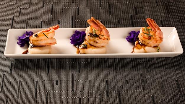 Grillowane krewetki z surową rybą do paznokci na białym talerzu przy stole