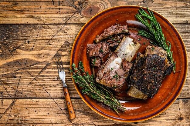 Grillowane krótkie żeberka wołowe z tymiankiem na rustykalnym talerzu. drewniane tła. widok z góry. skopiuj miejsce.