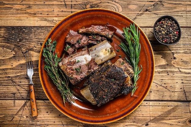 Grillowane, krótkie żeberka wołowe z tymiankiem na rustykalnym talerzu. drewniane tła. widok z góry.
