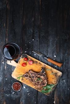 Grillowane mięso, soczysty kawałek wołowiny, kieliszek wytrawnego czerwonego wina.