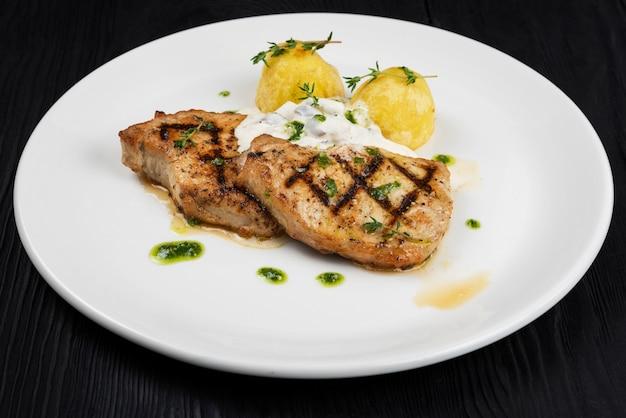 Grillowane mięso wieprzowe z sosem grzybowym i ziemniakami na białym talerzu na drewnianym czarnym tle