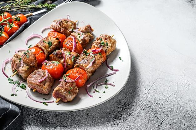 Grillowane mięso wieprzowo-wołowe na drewnianych szaszłykach.