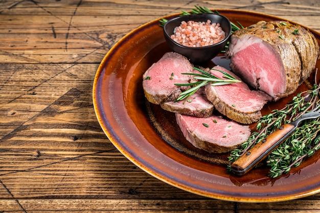 Grillowane mięso z polędwicy wołowej na rustykalnym talerzu z solą. tło. widok z góry. skopiuj miejsce.