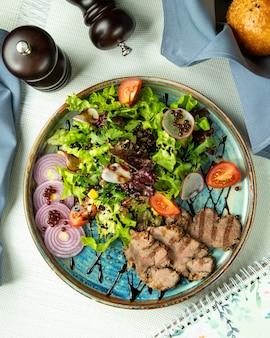 Grillowane mięso z surówką i cebulą na tacy