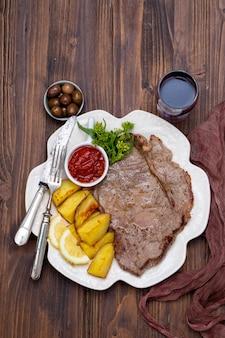 Grillowane mięso z ziemniakami i sosem na białym talerzu