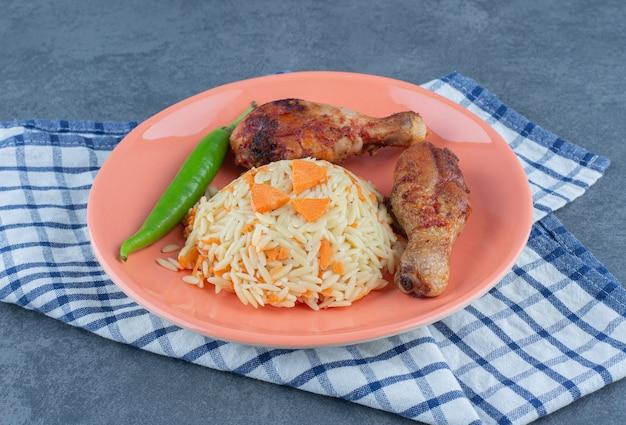 Grillowane nogi i doprawiony ryż na pomarańczowym talerzu.