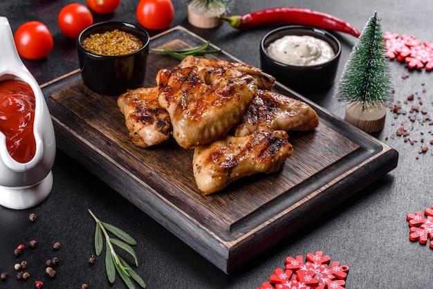 Grillowane pikantne skrzydełka z kurczaka na ciemnym tle z przyprawami i ziołami