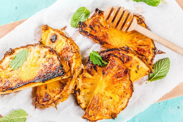 Grillowane plastry ananasa z miętowym sosem miodowo-limonkowym na jasnoniebieskim tle