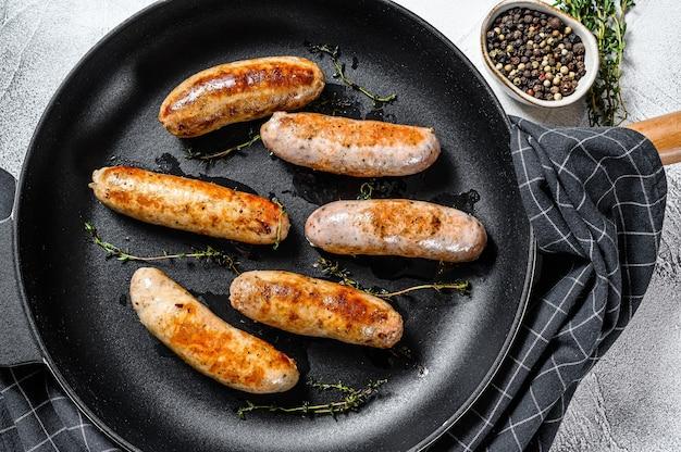 Grillowane różne kiełbaski wieprzowe, wołowe i drobiowe z przyprawami na patelni
