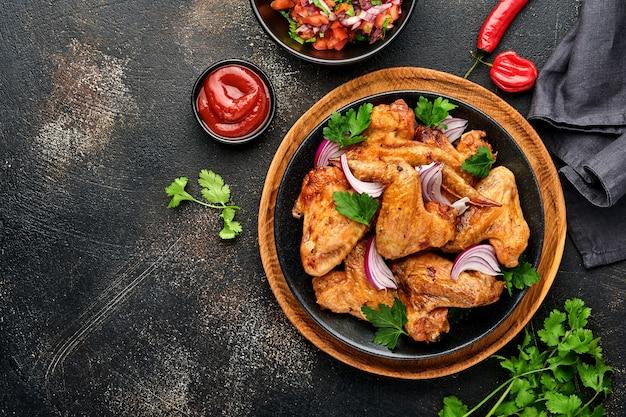 Grillowane skrzydełka z kurczaka lub pieczony grill z przyprawami i sosem salsa pomidorowa na czarnym talerzu.