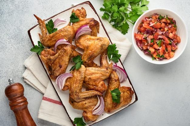 Grillowane skrzydełka z kurczaka lub pieczony grill z przyprawami i sosem salsa pomidorowa na talerzu