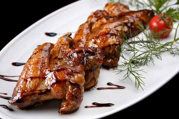 Grillowane skrzydełka z kurczaka na białym talerzu, na czarnym tle, z pomidorem i koperkiem