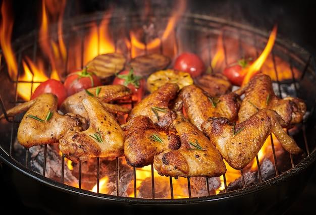 Grillowane skrzydełka z kurczaka na płonącym grillu z grillowanymi warzywami w sosie barbecue z pieprzem rozmarynem, solą. widok z góry z miejscem na kopię.