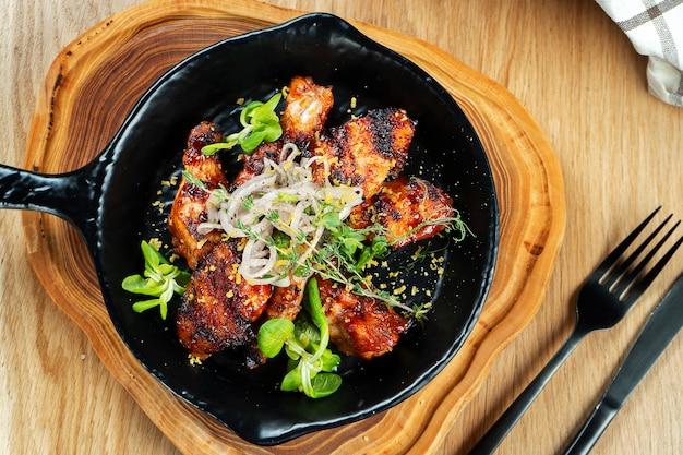 Grillowane skrzydełka z kurczaka w sosie miodowo-piwnym podawane na ozdobnej patelni z ziołami. z bliska, selektywne focus. drewniany mur. zdjęcie jedzenia