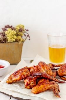 Grillowane skrzydełka z kurczaka z piwem i czerwonym sosem na drewnianym tle. przekąska do piwa. grill. przepisy
