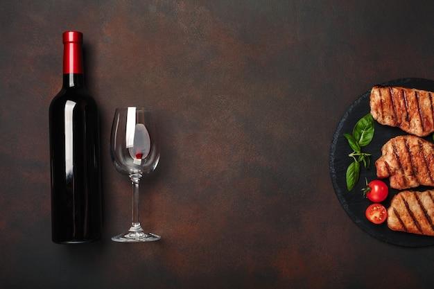 Grillowane steki wieprzowe na kamieniu z butelką wina, kieliszek do wina, nóż i widelec na zardzewiałym tle