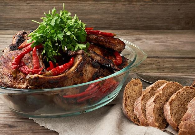Grillowane steki wieprzowe na kości leżą w przezroczystym szklanym talerzu na drewnianym stole