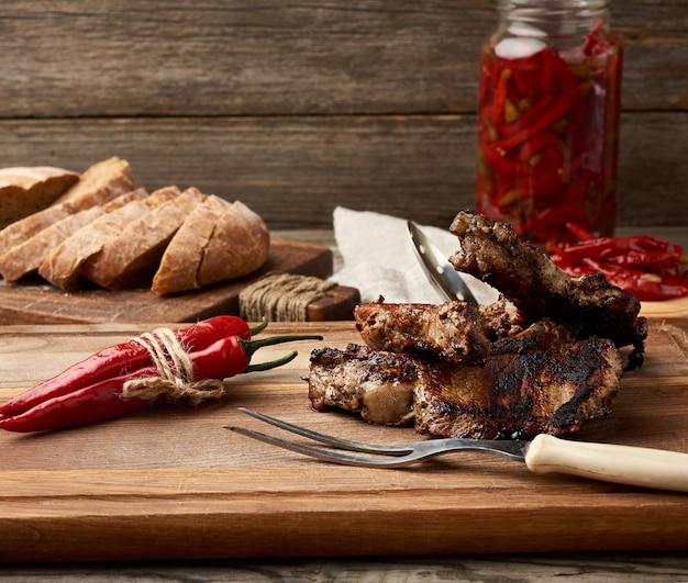 Grillowane steki wieprzowe na krawędzi leżą na kuchennej desce do krojenia