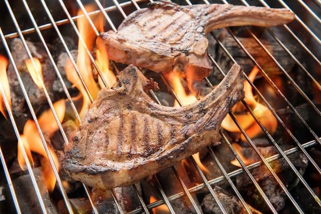 Grillowane steki wieprzowe nad płomieniami na grillu.