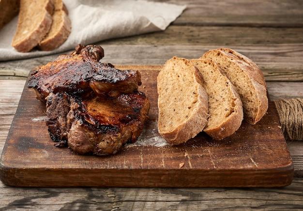 Grillowane steki wieprzowe z kością na kuchennej desce do krojenia, piec