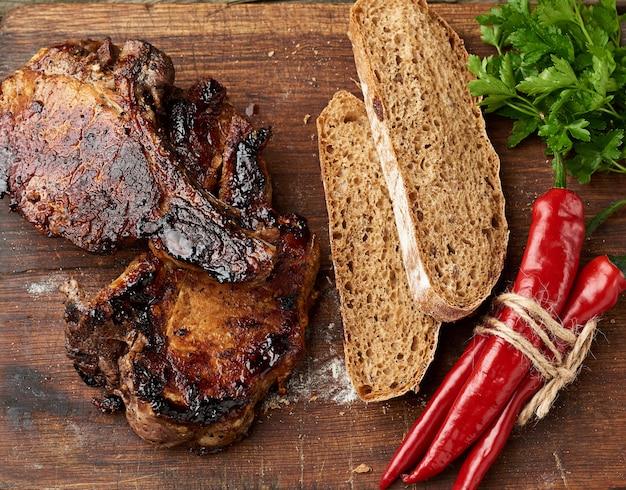Grillowane steki wieprzowe z kością na kuchennej desce do krojenia, pieczony chleb żytniej mąki