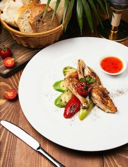 Grillowane steki z kurczaka i warzywa w białym talerzu z sosem