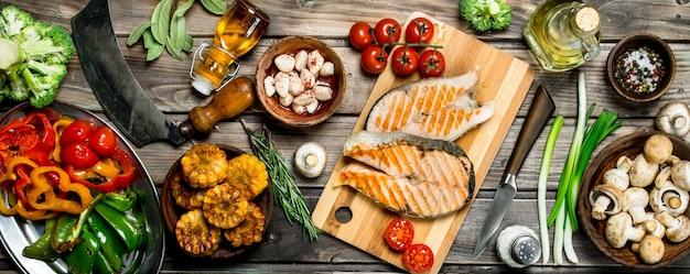 Grillowane steki z łososia z różnymi warzywami i przyprawami. na drewnianym stole.