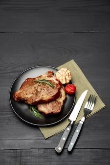 Grillowane steki z pieczonej wołowiny na czarnym talerzu ceramicznym